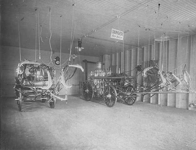 Photo of fire station interior showing horse-drawn pumper and wagon for equipment, ca. 1900.