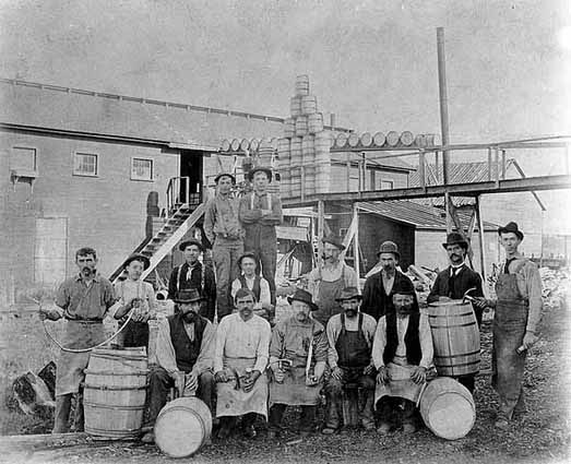 Photo of male workers posed with their barrels outside a cooperage, 1902.