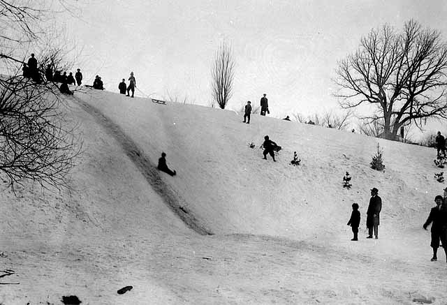 Photo of snowy hill with children sledding.