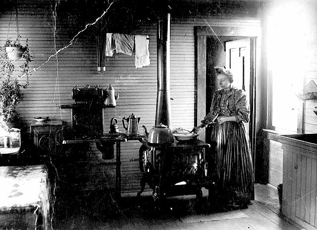 Photo of woman cooking at kitchen stove, 1890.