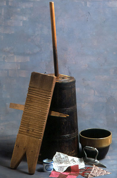Color photo of a butter churn, washboard, mixing bowl, child's cup, flat iron, and quilt squares.
