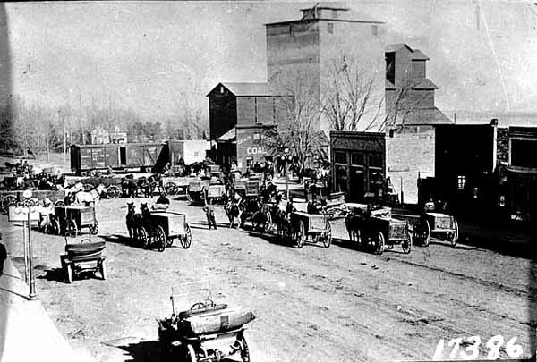 Photo of wagons full of wheat converging at a grain elevator with a train, ca. 1910.