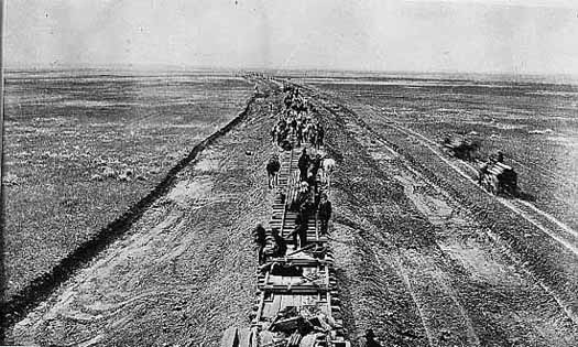 Photo of crew laying down a railroad line on the prairie, 1887.