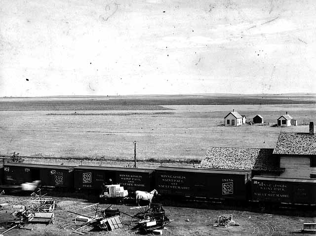 Photo of farm implements after being removed from a train in the prairie, 1895.
