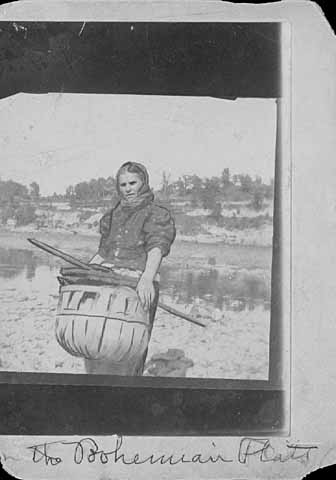 Photo of woman near the Mississippi river, carrying a basket of wood, ca. 1900.
