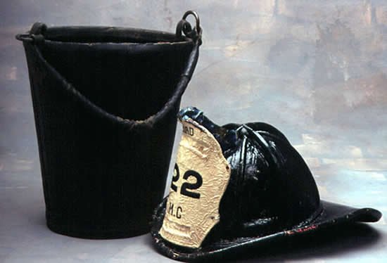 Color photo of a fireman's helmet and a leather bucket.