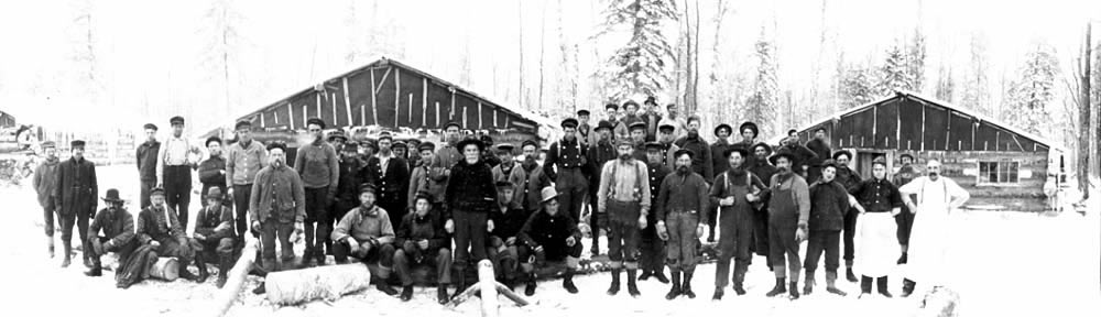 Photo of lumber crew and cooks posing infront of camp buildings, ca. 1900-1920.