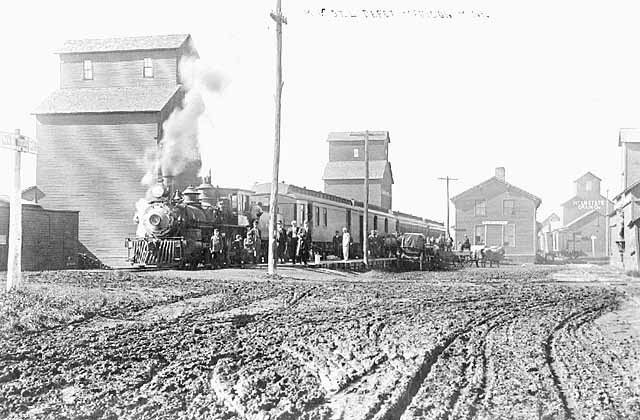 Photo of a town on Minnesota's western boarder showing dirt roads, a train, and a grain elevator, ca. 1890.