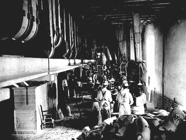 Photo of the flour-packing floor at the Pillsbury A Mill, two workers in foreground wear aprons and hats, 1902.