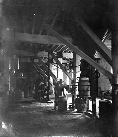 Photo of worker loading flour into a barrel on the packing floor at the Washburn A Mill, ca. 1875.
