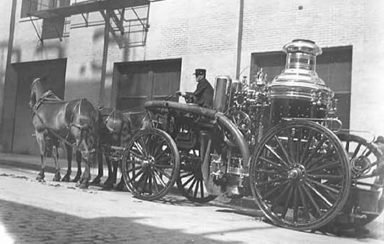 Photo of a fireman posed with a horse-drawn fire engine, 1905.