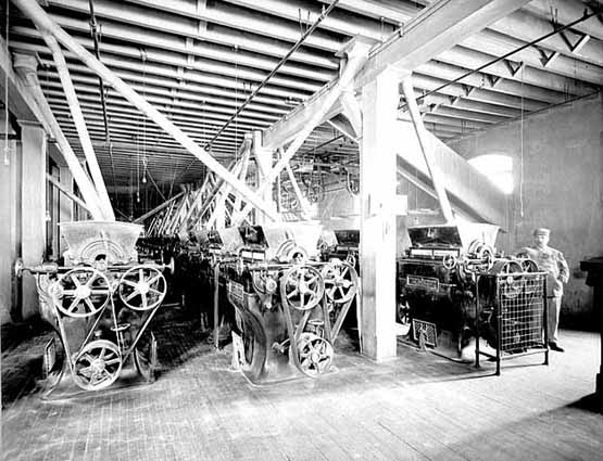 Photo of Pillsbury-Washburn mill interior showing three rows of roller mill stands and one worker, 1897.