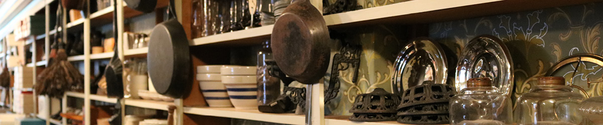 Cast iron pans, glassware, and ceramic bowls sit stacked on shelves.