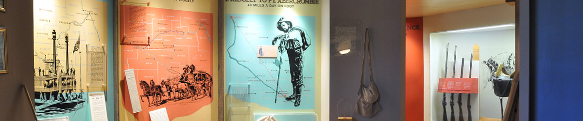 Exhibit boards with images of an ancient boat, carriage and a figure of a person who went 40 miles a day on foot.