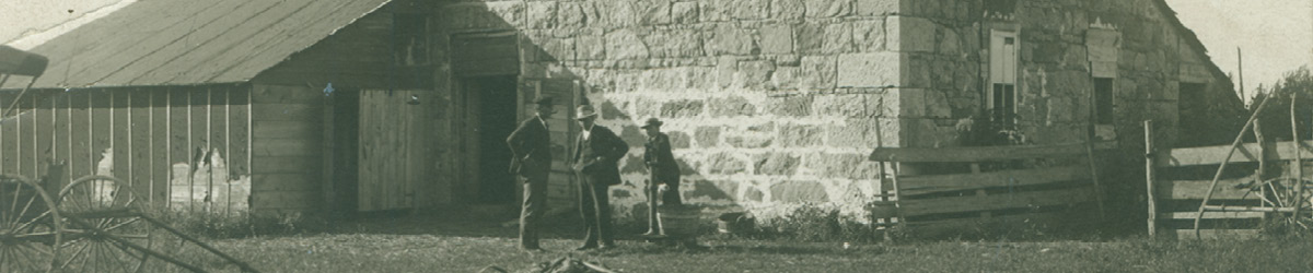Historic photo of three people standing in front of an outpost building.