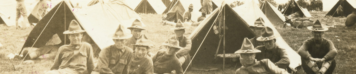 Historic photo of soldiers sitting on the ground in front of tents.