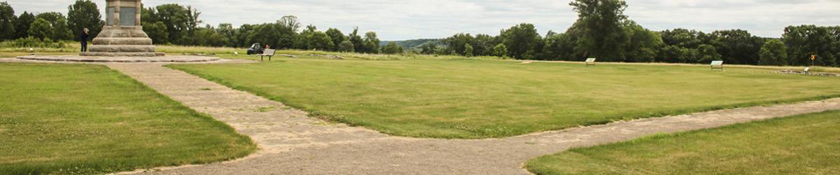 A four way path on a big lawn.
