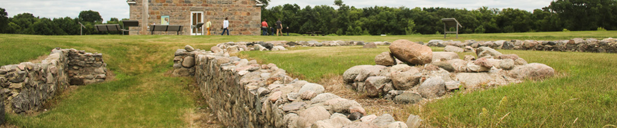 Two short rock walls and a pile of rocks outside a historic house.