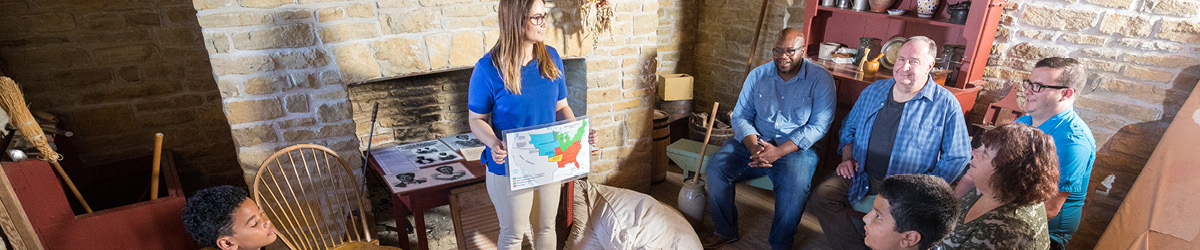 A Fort Snelling staff person teaching a group of visitors about Dred and Harriet Scott.