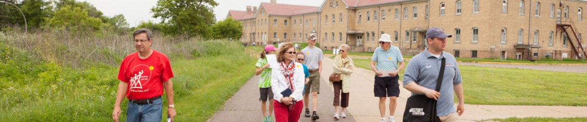 A tour group follows a Fort Snelling guide past the historic barracks.