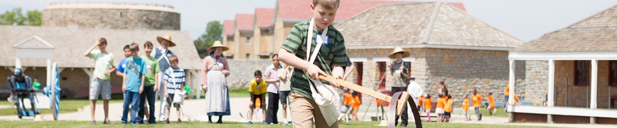 A group of children play historic yard games on the lawn of Fort Snelling.