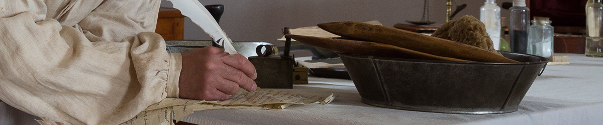A hand writing with a quill pen alongside historic objects.