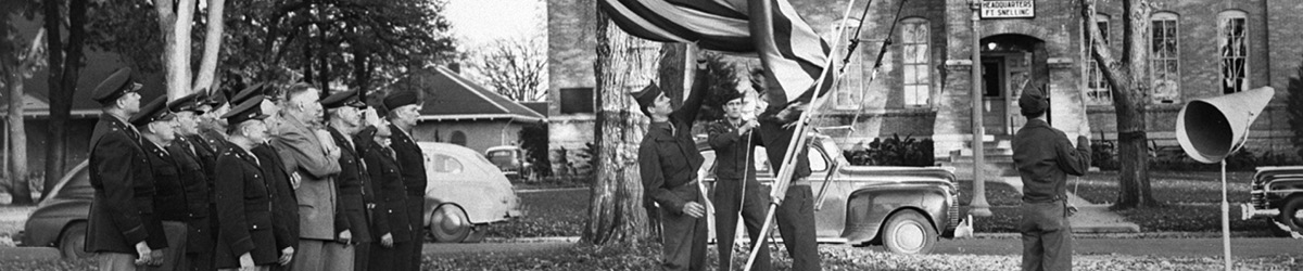 soldiers raising flag up a pole