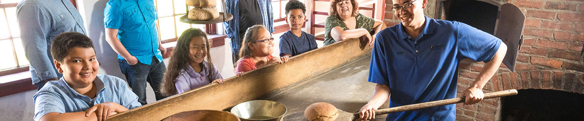 A Fort Snelling staff person baking bread in a historic oven as visitors watch.