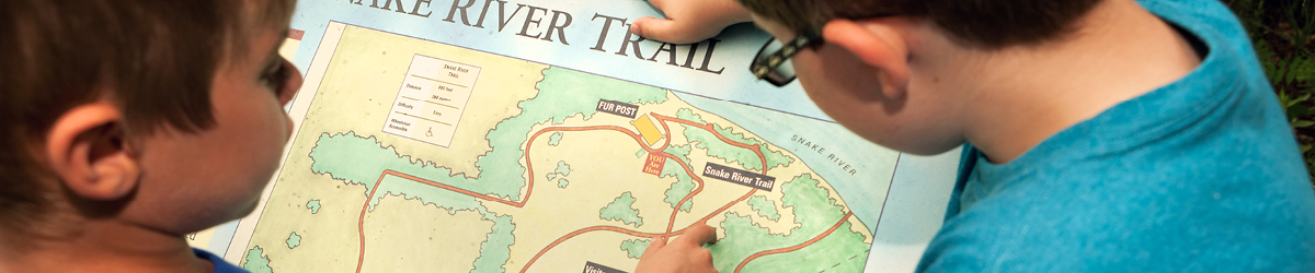 Two boys look over a Snake River Trail map.