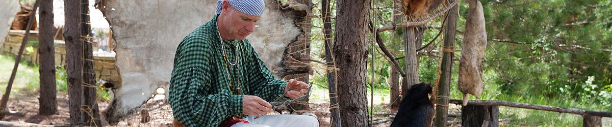 A costumed interpreter demonstrating pelt stitching.
