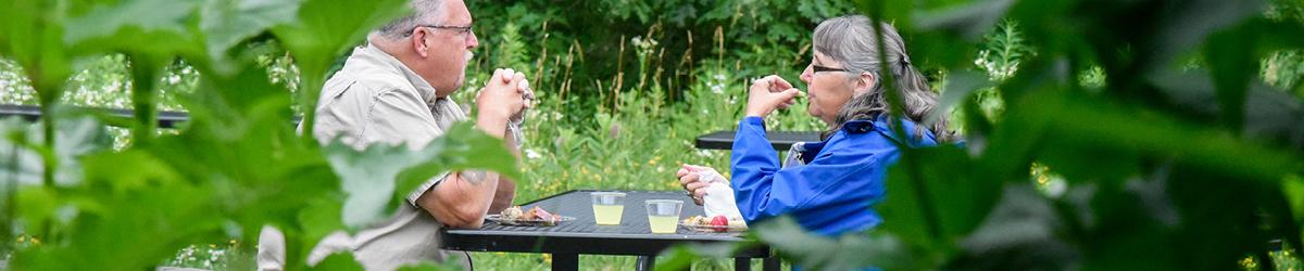A man and woman eating at a picnic table.
