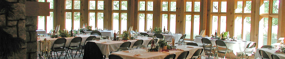 Tidily placed tables and chairs behind glass doors, ready for an event.