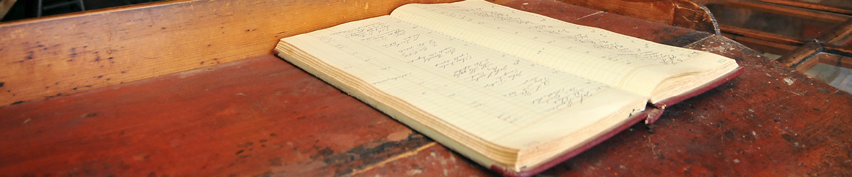 An open notebook facing up on top of a wood table.