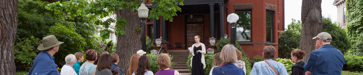 A group of adults face a tour guide as they stand on the sidewalk in front of a large house.