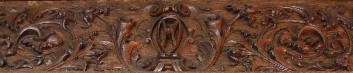 Detail of intricate wood carving, with the letter H in the center.
