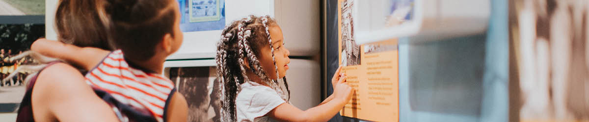 A child points at and examines a photograph on an exhibit wall.