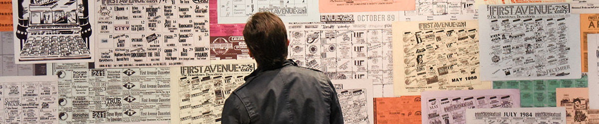 A man looks at music posters on an exhibit wall.