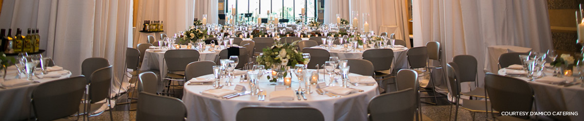 Several round tables are set with fine linens, crystal stemware, and floral centerpieces in preparation for a formal event.