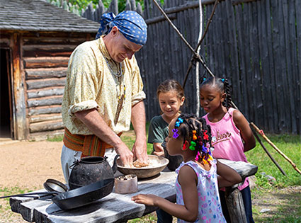 Three children observe a Fur Post interpreter mix dough in a bowl.