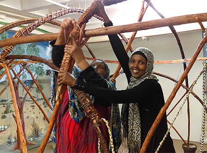 Two women help construct part of the Somali exhibit.
