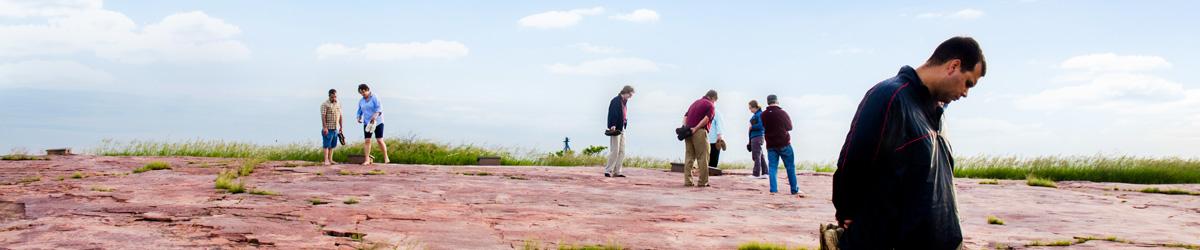 People look at rock carvings.