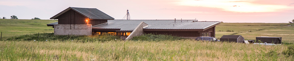 View of Jeffers Petroglyphs visitor center sitting in the middle of prairie land with the sun setting in the background.