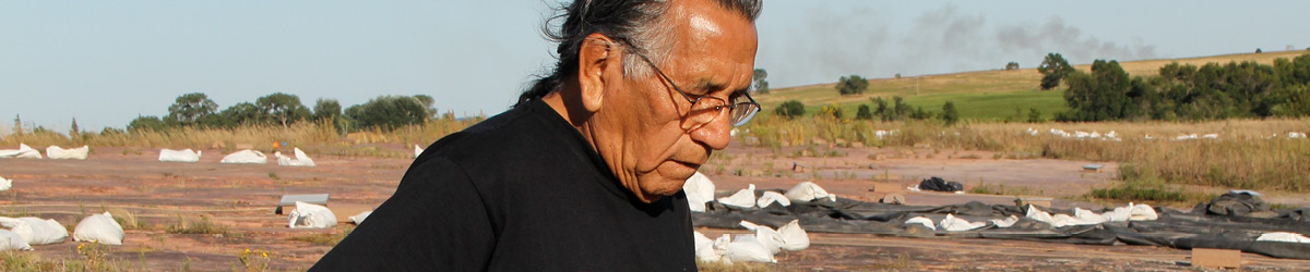 A man wearing glasses looking down the ground, with a red rock prairie in the background.