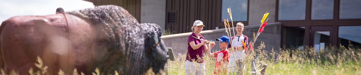 "In the background, two boys get assistance from a volunteer in throwing ""spears,"" while a bison replica stands in the foreground."