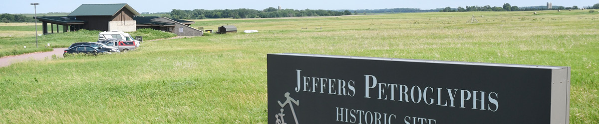 Sign of Jeffers Petroglyphs with the visitor center and some cars at the background.