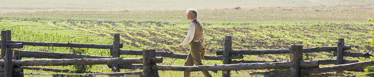 A farmer walking between two wooden fences
