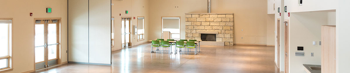 A tall open room with a large fireplace and a table with eight green chairs