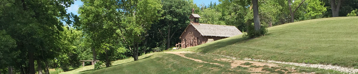 On a hill with green trees, there is Lac qui Parle Mission.