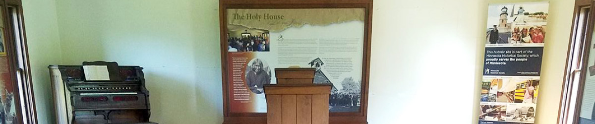 Interior of Lac qui Parle Mission with a piano, a podium, and a banner stand.