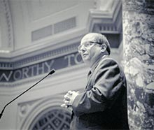 Senator Allan Spear speaking into a microphone.